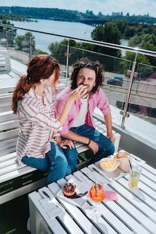 Batatas fritas e coquetéis. vista superior de um casal elegante e moderno se sentindo relaxado enquanto come batatas fritas e bebe