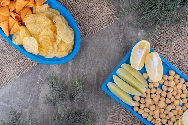 Batatas fritas e diversos petiscos em pratos azuis