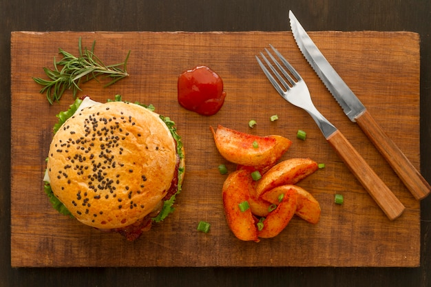 Batatas fritas e hambúrguer na placa de madeira