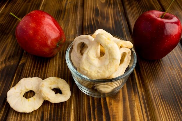 Batatas fritas e maçãs vermelhas na mesa de madeira
