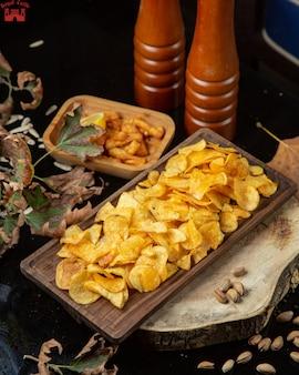 Batatas fritas e moedores de especiarias em cima da mesa