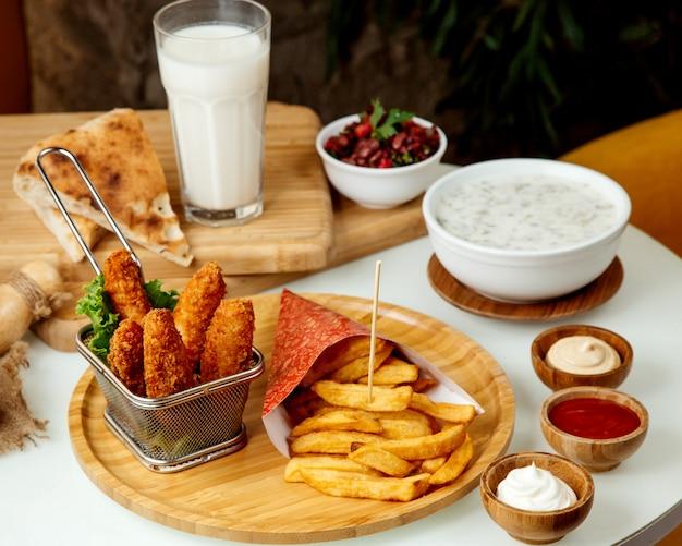Batatas fritas e nuggets de frango em massa em uma placa de madeira