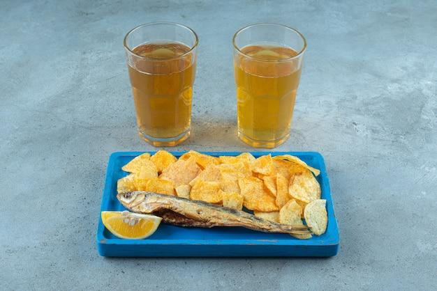 Batatas fritas e peixe na placa de madeira ao lado de dois copos de cerveja no mármore.