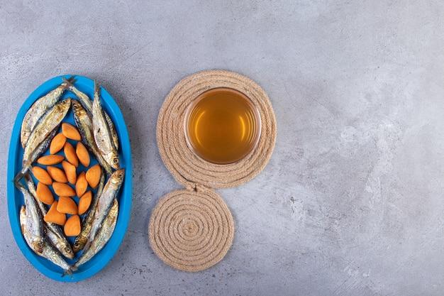 Batatas fritas e peixe seco em uma placa de madeira ao lado de um copo de cerveja em um tripé, no fundo de mármore.