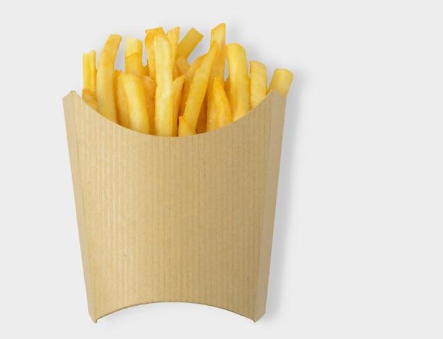 Batatas fritas em caixa de papel kraft em branco sobre fundo branco. trajeto de recorte incluído no fundo branco.