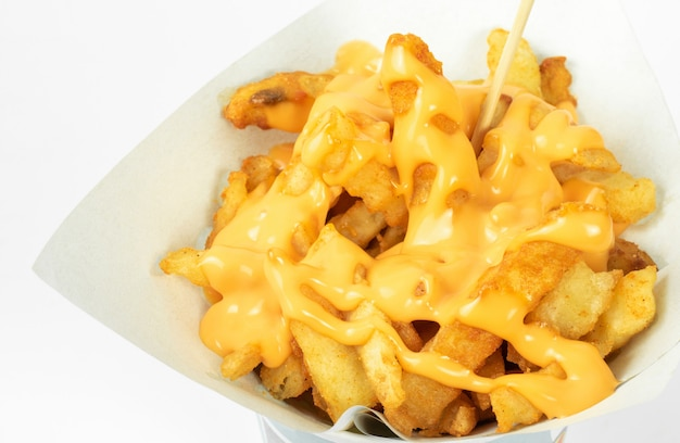 Batatas fritas em copo branco com molho de queijo no fundo branco