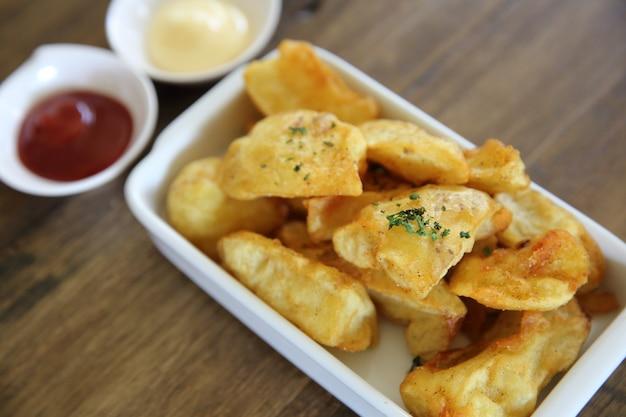 Batatas fritas em fundo de madeira