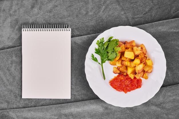 Batatas fritas em molho de tomate com um livro de receitas.