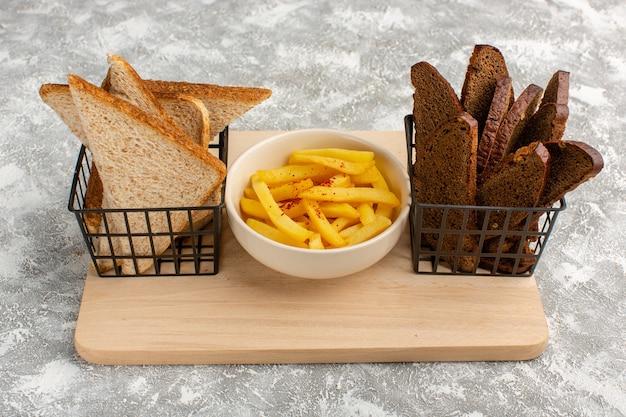 Batatas fritas em prato branco junto com pão preto e branco