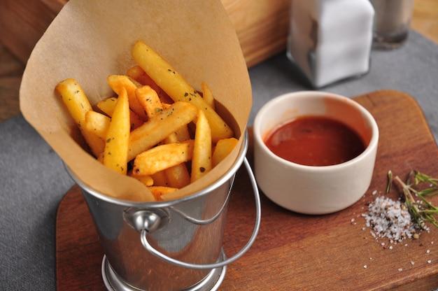 Batatas fritas em um balde de metal com molho de tomate