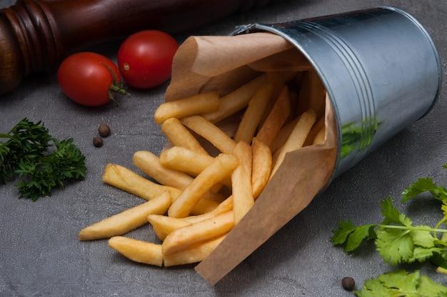 Batatas fritas em um balde de metal em um fundo cinza
