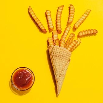 Batatas fritas em um cone no fundo amarelo
