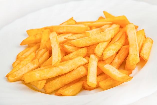 Batatas fritas em um prato, isolado no branco.
