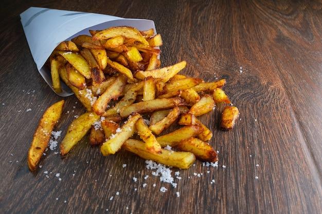 Batatas fritas em um saco de papel com molhos na terra traseira de madeira