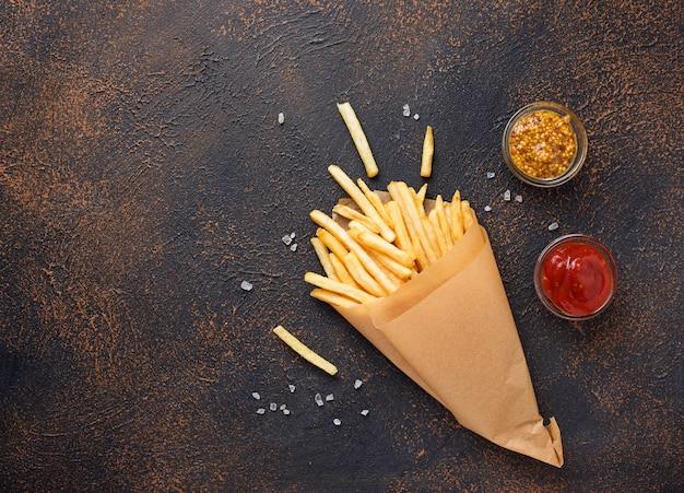 Batatas fritas em um saco de papel com molhos