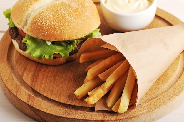 Batatas fritas em um saco de papel e um hambúrguer