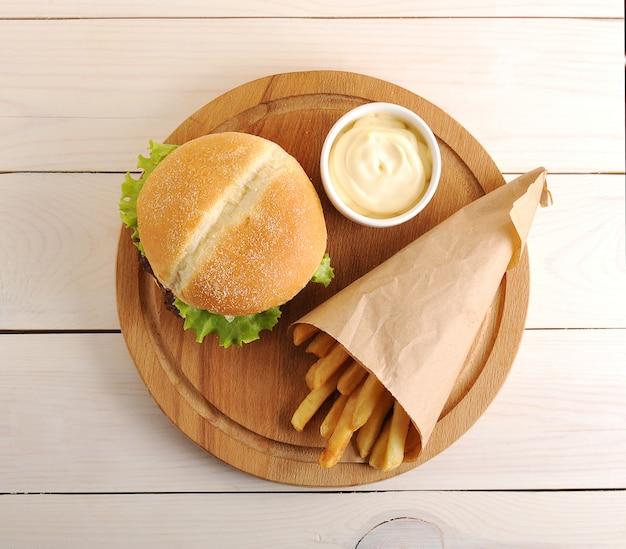 Batatas fritas em um saco de papel, molho de queijo e hambúrguer