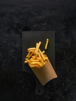 Batatas fritas em uma caixa de papel artesanal na placa de madeira, vista superior com espaço de cópia