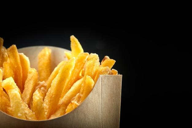 Batatas fritas em uma cesta de papel. fast-food. batatas fritas em uma caixa de papel na parede preta