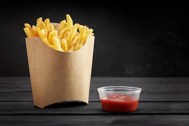 Batatas fritas em uma cesta de papel. fast-food. batatas fritas em uma caixa de papel no espaço preto
