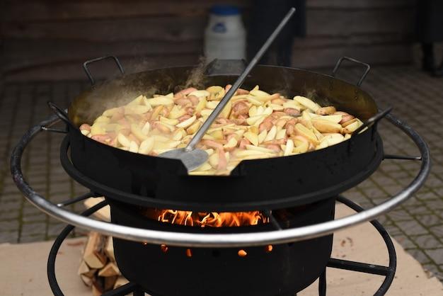 Batatas fritas em uma enorme wok em fogo alto