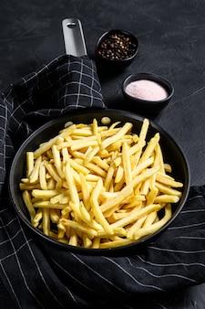 Batatas fritas em uma frigideira. fundo preto. vista do topo