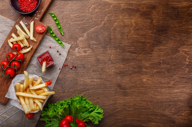 Batatas fritas em uma grade com ketchup, salada e tomate cereja na mesa de madeira marrom