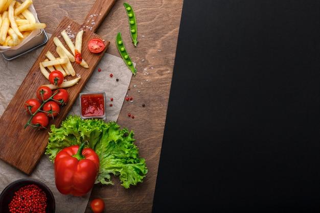 Batatas fritas em uma grade com ketchup, salada e tomate cereja na mesa de madeira