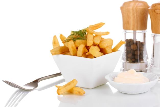 Batatas fritas em uma tigela isolada no branco