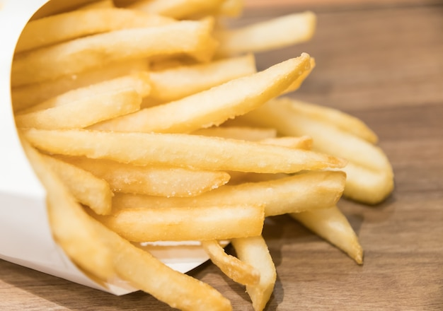 Batatas fritas frescas fritas com ketchup em fundo de madeira Foto Premium