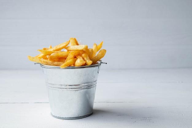 Batatas fritas frescas na mesa de madeira branca