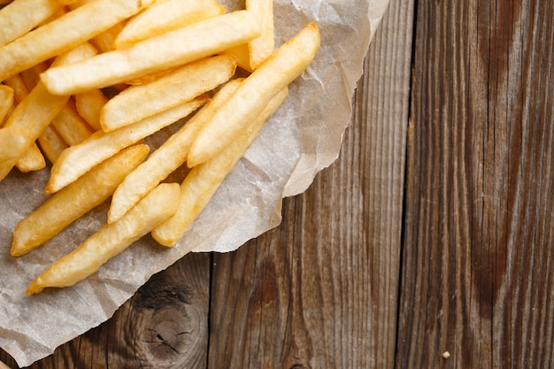 Batatas fritas frescas no fundo da mesa de madeira