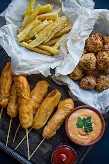 Batatas fritas fritadas, cão de milho e croquetes e batatas do repolho com molho e ketchup.