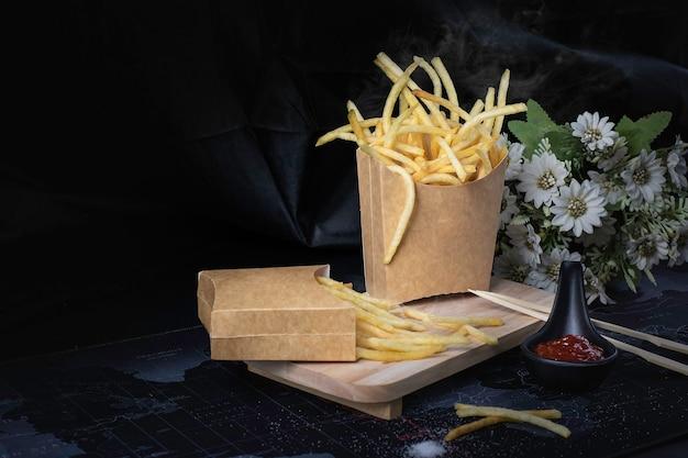 Batatas fritas fritas amarelas em um fundo preto com fumaça