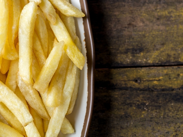 Batatas fritas fritas em um prato branco com borda marrom na mesa de madeira