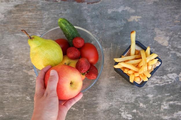 Batatas fritas frutas vegetais conceito de escolha de nutrição correta ou de comer lixo