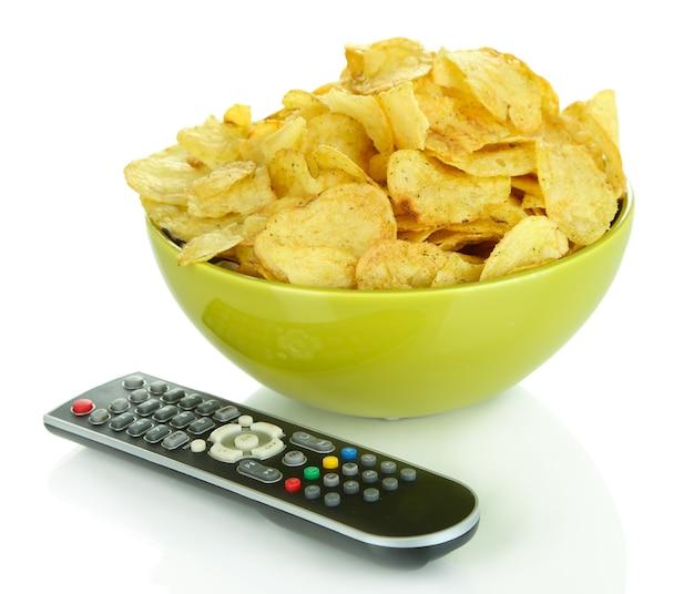 Batatas fritas na tigela e controle remoto da tv isolado no branco