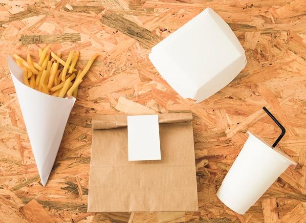 Batatas fritas no cone de papel e maquete de pacote em pano de fundo de madeira