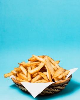Batatas fritas no fundo azul com espaço da cópia