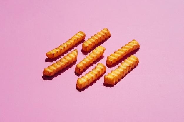 Batatas fritas no fundo rosa