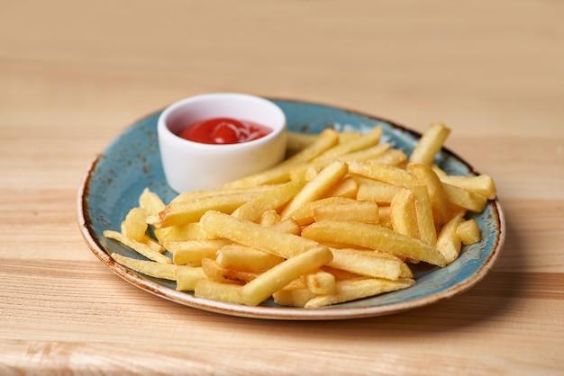 Batatas fritas no prato de pé na mesa de madeira.
