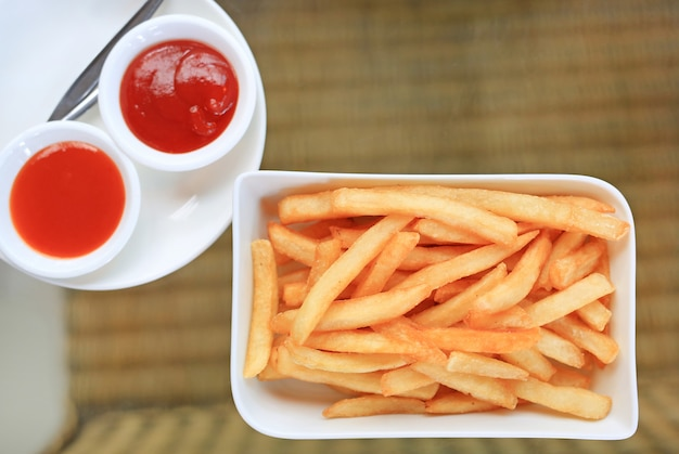 Batatas fritas no saque branco da placa com molho do pimentão e de tomate na tabela. acima vista.