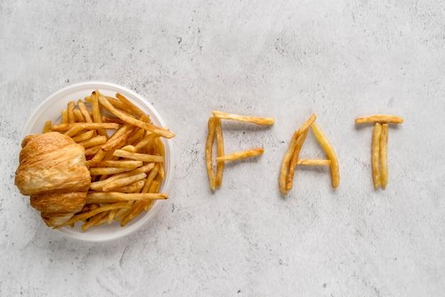 Batatas fritas; pão de croissant e gordura de enfermaria sobre superfície texturizada
