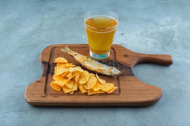Batatas fritas, peixe e copo de cerveja em uma placa, no fundo de mármore.