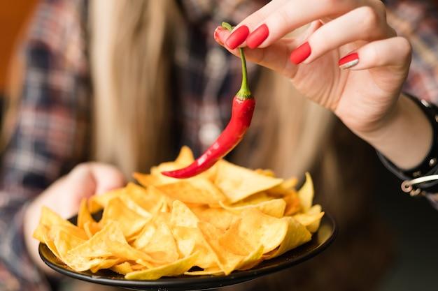 Batatas fritas picantes. lanche de comida ardente e picante. mão de uma mulher segurando batatas fritas de nacho e pimenta malagueta vermelha
