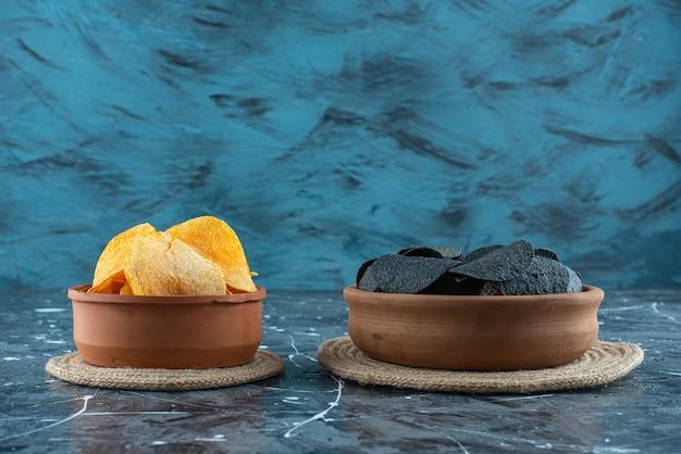 Batatas fritas pretas e batatas fritas em uma tigela sobre tripés em mármore.