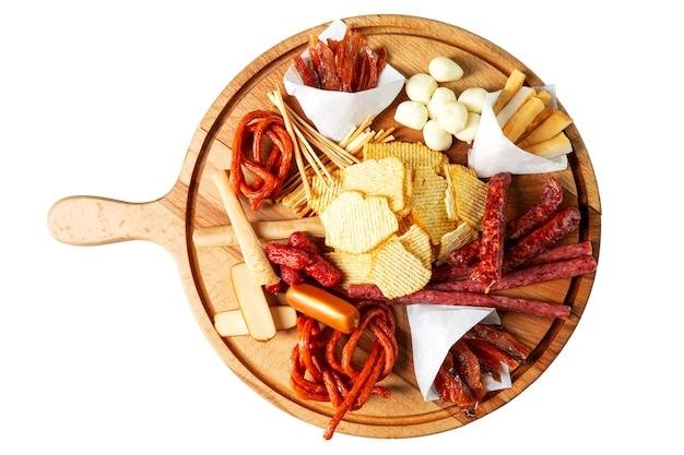 Batatas fritas, salsichas e queijos em uma placa de madeira
