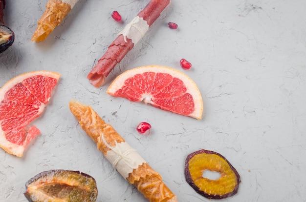 Batatas fritas secas variadas e frutas maduras em fundo cinza. batatas fritas de frutas. conceito de alimentação saudável, lanche, sem açúcar. vista superior, copie o espaço.