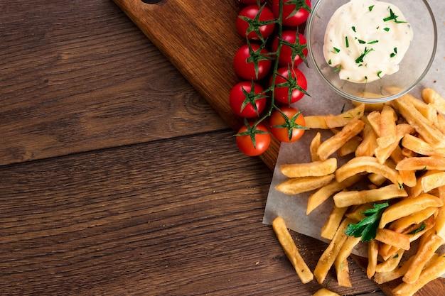 Batatas fritas, tomate cereja, molho de alho na madeira