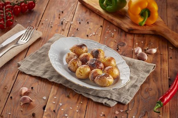 Batatas grelhadas para churrasco, fundo de madeira